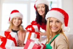 Femmes dans des chapeaux d'aide de Santa avec beaucoup de boîte-cadeau Image libre de droits