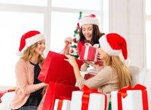 Femmes dans des chapeaux d'aide de Santa avec des paniers Photographie stock