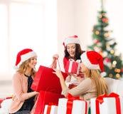 Femmes dans des chapeaux d'aide de Santa avec des paniers Photo libre de droits