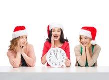 Femmes dans des chapeaux d'aide de Santa avec l'horloge montrant 12 Photo stock