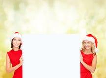 Femmes dans des chapeaux d'aide de Santa avec le conseil blanc vide Photographie stock libre de droits