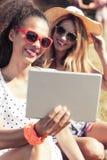 Femmes dans des lunettes de soleil prenant le selfie avec le comprimé Photographie stock