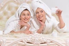 Femmes dans des peignoirs faisant le selfie Photographie stock