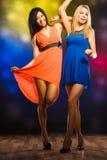Femmes dans des robes de soirée dansant dans le club Photos libres de droits