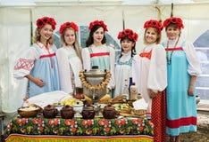 Femmes dans des vêtements nationaux, se tenant à une table avec un samovar Photographie stock
