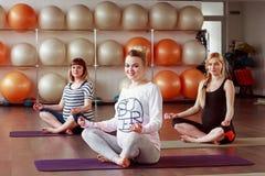 Femmes dans l'expectative caucasiennes asseyant sur des tapis de yoga Photo stock