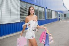 Femmes dans la robe blanche avec des paniers Sourire heureux après l'achat des présents Plaisir d'achat Photographie stock