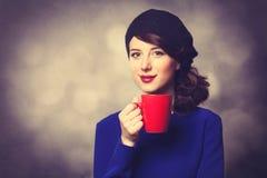 Femmes dans la robe bleue avec la tasse rouge Image stock