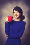 Femmes dans la robe bleue avec la tasse rouge Images libres de droits