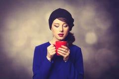 Femmes dans la robe bleue avec la tasse rouge Photographie stock libre de droits