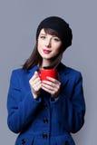 Femmes dans la robe bleue avec la tasse rouge Photographie stock