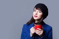Femmes dans la robe bleue avec la tasse rouge Photo libre de droits
