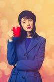 Femmes dans la robe bleue avec la tasse rouge Photos libres de droits