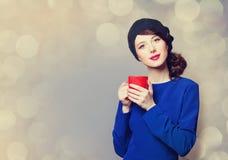 Femmes dans la robe bleue avec la tasse rouge Photo stock