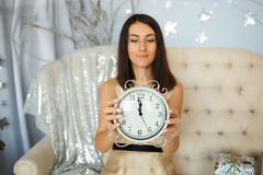 Femmes dans la robe d'or tenant une horloge Photo libre de droits
