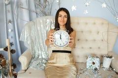 Femmes dans la robe d'or tenant une horloge Images libres de droits
