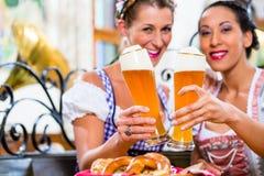 Femmes dans le bar bavarois grillant avec de la bière de blé Photos stock