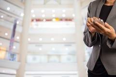 Femmes dans le centre commercial utilisant le téléphone portable Images stock