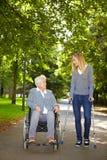 Femmes dans le fauteuil roulant et sur des béquilles Photo stock
