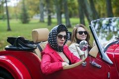 Femmes dans le noir sur la rétro voiture rouge Image stock