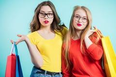 Femmes dans les achats Deux belles filles dans des vêtements lumineux avec des verres regardant l'appareil-photo Images libres de droits