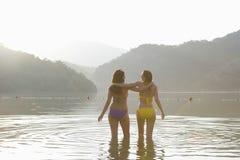 Femmes de bikini avec des bras autour de la position dans le lac Photographie stock