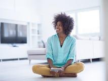 Femmes de couleur à l'aide de la tablette sur le plancher à la maison image libre de droits