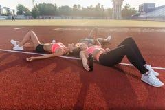Femmes de forme physique détendant après la formation Séance d'entraînement menteuse d'athlètes fatigués ensemble en cercle dans  Photo stock
