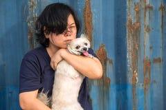 Femmes de l'Asie et étreindre heureux de chien avec le récipient Photos stock