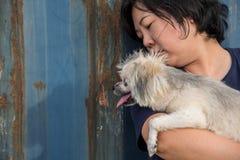 Femmes de l'Asie et étreindre heureux de chien avec le récipient Image stock
