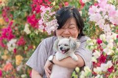 Femmes de l'Asie et étreindre heureux de sourire de chien Photographie stock