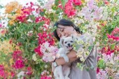 Femmes de l'Asie et étreindre heureux de sourire de chien Photo stock