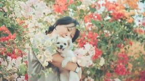 Femmes de l'Asie et étreindre heureux de sourire de chien Photo libre de droits