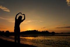 Femmes de silhouette dans l'amour sur la plage Images libres de droits