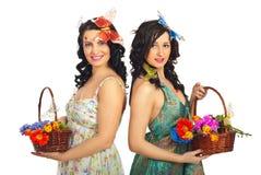 Femmes de source retenant des paniers de fleurs Image stock