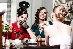Femmes de sourire élégantes parlant et buvant du café Photographie stock