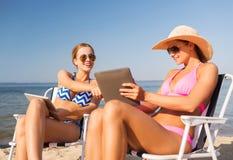 Femmes de sourire avec des ordinateurs de PC de comprimés sur la plage Photographie stock