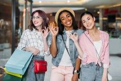 Femmes de sourire avec des paniers montrant les signes corrects au centre commercial Photos stock