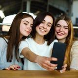 Femmes de sourire ayant l'amusement et prendre le selfie au café Images stock
