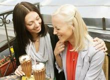 Femmes de sourire buvant d'un café Image libre de droits