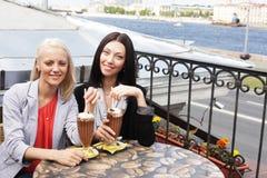 Femmes de sourire buvant d'un café Photographie stock