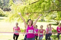 Femmes de sourire courant pour la conscience de cancer du sein Photos stock