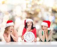 Femmes de sourire dans des chapeaux d'aide de Santa avec l'horloge Photographie stock libre de droits
