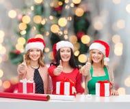 Femmes de sourire dans des chapeaux d'aide de Santa emballant des cadeaux Photos libres de droits