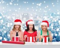 Femmes de sourire dans des chapeaux d'aide de Santa emballant des cadeaux Photos stock