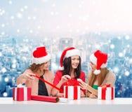 Femmes de sourire dans des chapeaux d'aide de Santa emballant des cadeaux Images stock