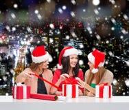 Femmes de sourire dans des chapeaux d'aide de Santa emballant des cadeaux Image stock