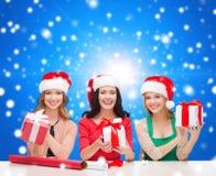Femmes de sourire dans des chapeaux d'aide de Santa emballant des cadeaux Photographie stock