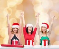 Femmes de sourire dans des chapeaux d'aide de Santa emballant des cadeaux Photo stock