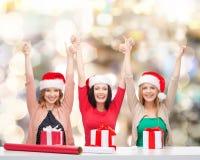 Femmes de sourire dans des chapeaux d'aide de Santa emballant des cadeaux Image libre de droits